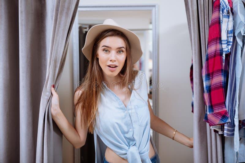 Glückliche junge Frau, die auf Kleidung in der Umkleidekabine versucht stockbilder