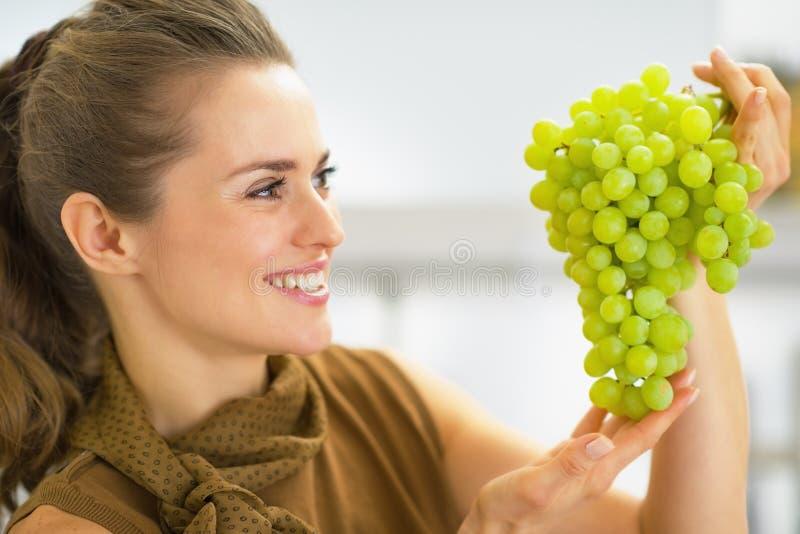 Glückliche junge Frau, die auf Niederlassung von Trauben schaut stockfoto