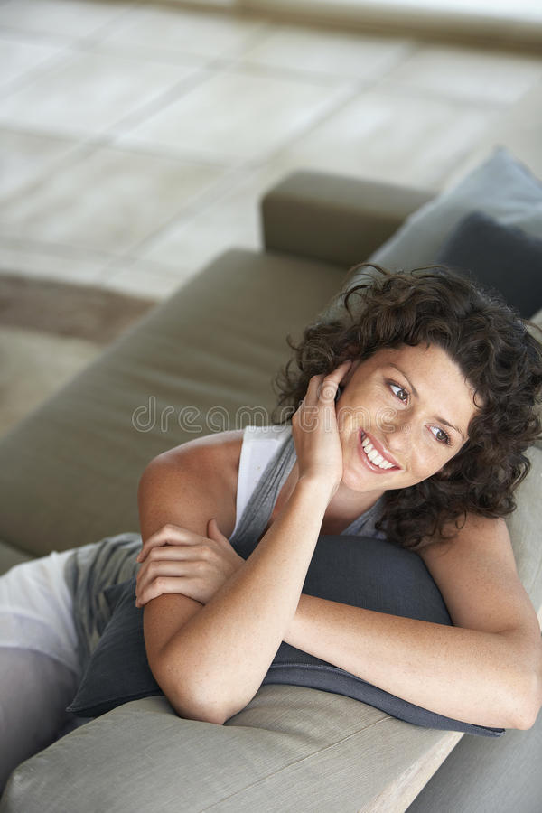 Glückliche junge Frau, die bei der Entspannung auf Couch weg schaut lizenzfreie stockfotos