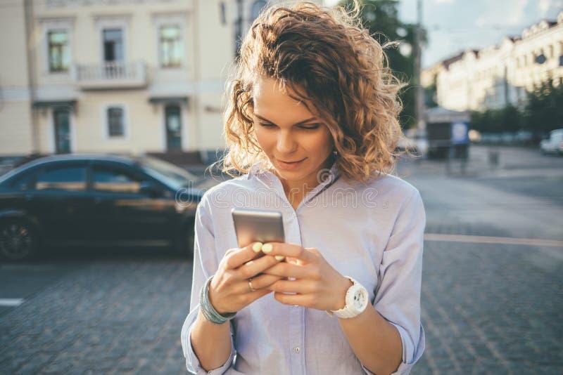 Glückliche junge Frau, die blaues Hemd unter Verwendung des Handys trägt lizenzfreies stockfoto