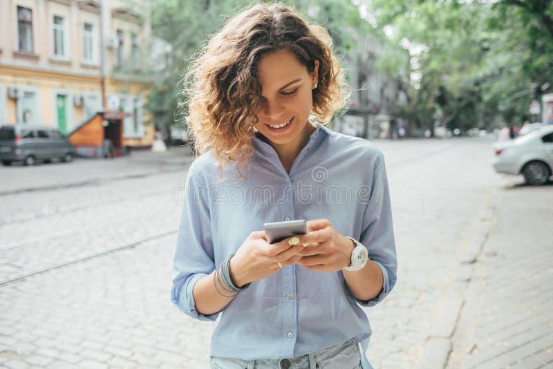 Glückliche junge Frau, die blaues Hemd unter Verwendung des Handys trägt lizenzfreie stockfotos