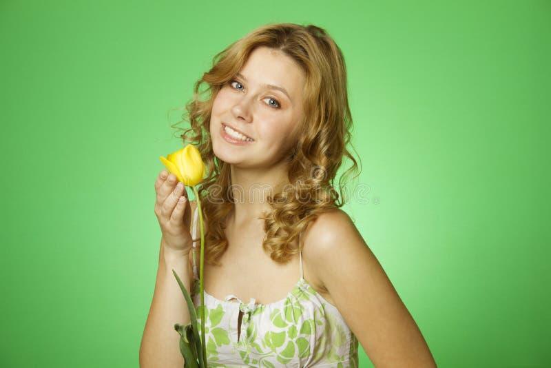 Glückliche junge Frau, die Blume umarmt lizenzfreie stockbilder