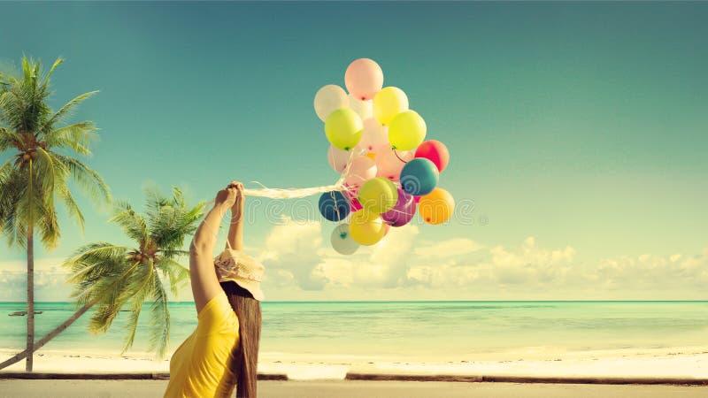 Glückliche junge Frau, die bunte Ballone mit dem Schwimmen hält, stockfotografie