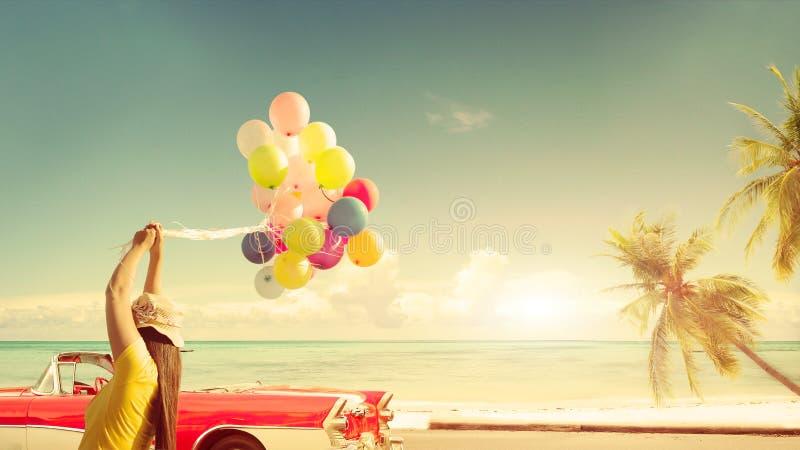 Glückliche junge Frau, die bunte Ballone mit dem Schwimmen hält stockfotografie