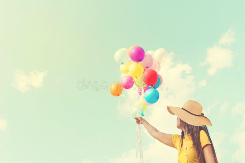 Glückliche junge Frau, die bunte Ballone mit dem Schwimmen hält lizenzfreies stockfoto