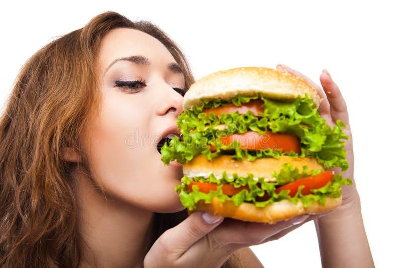Glückliche junge Frau, die den großen leckeren Burger lokalisiert isst lizenzfreie stockfotos
