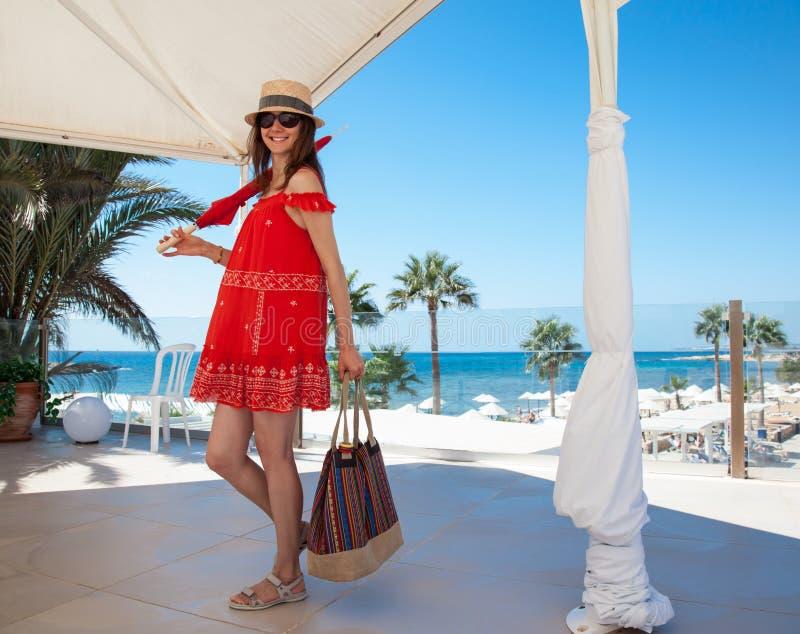 Glückliche junge Frau, die in den roten sundress halten eine Tasche und ein umbrel ist lizenzfreie stockbilder