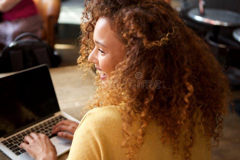 Glückliche junge Frau, die in der Caféfunktion mit Laptop sitzt stockbilder