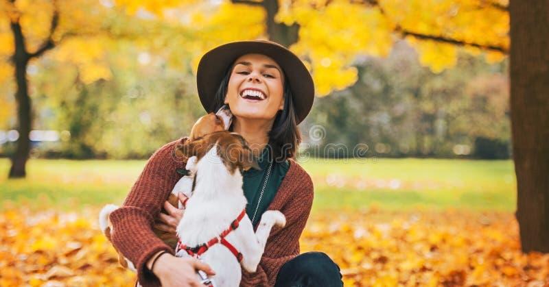 Glückliche junge Frau, die draußen mit Hund im Herbst spielt stockbilder