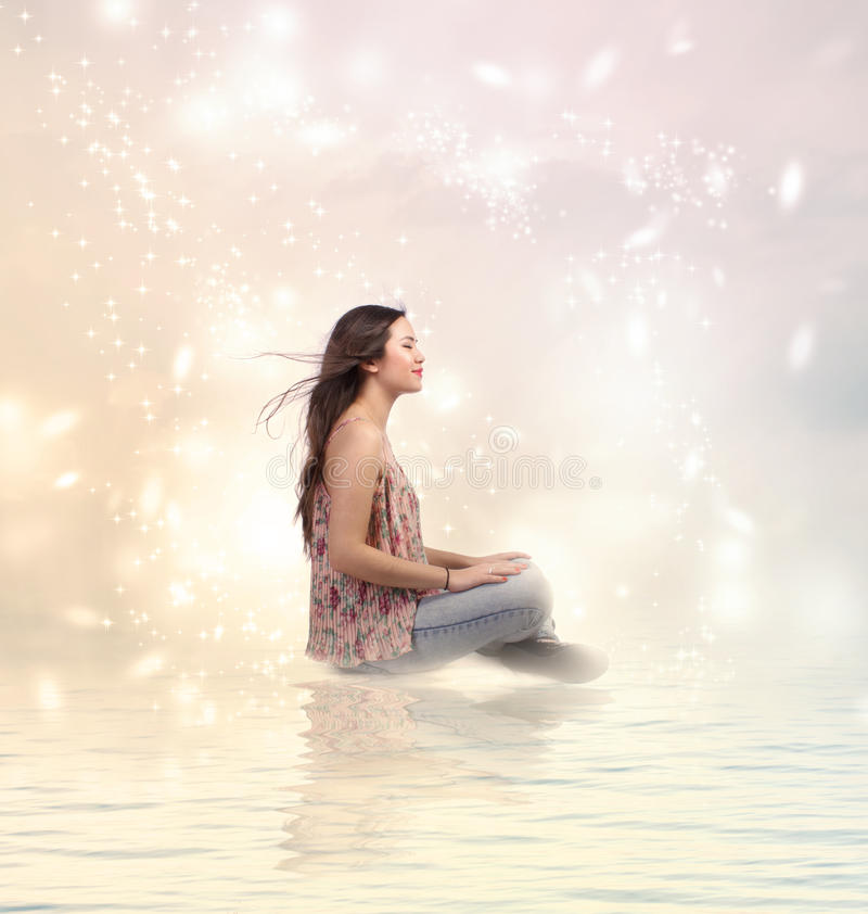 Glückliche junge Frau, die durch das Wasser sitzt lizenzfreie stockfotografie