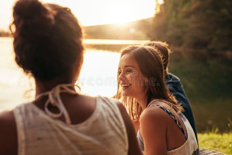 Glückliche junge Frau, die durch einen See mit ihren Freunden sitzt stockfotografie