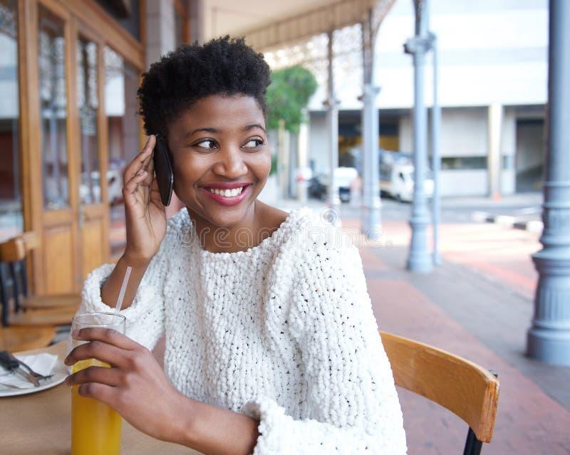 Glückliche junge Frau, die durch Handy am Restaurant nennt stockfotos