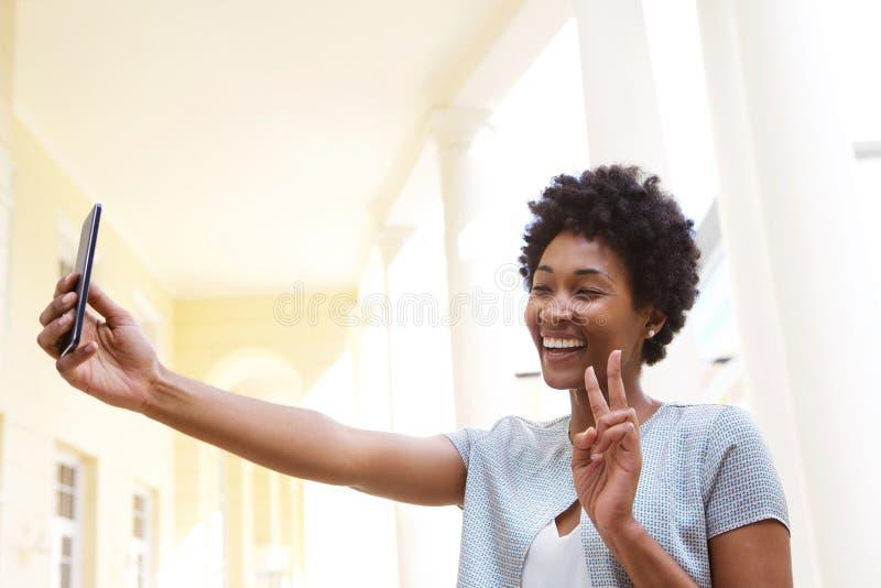 Glückliche junge Frau, die ein Friedenszeichen gestikuliert und selfie nimmt stockfoto