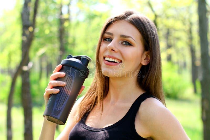 Glückliche junge Frau, die ein Glas Wasser in einem Sommerpark hält lizenzfreie stockbilder