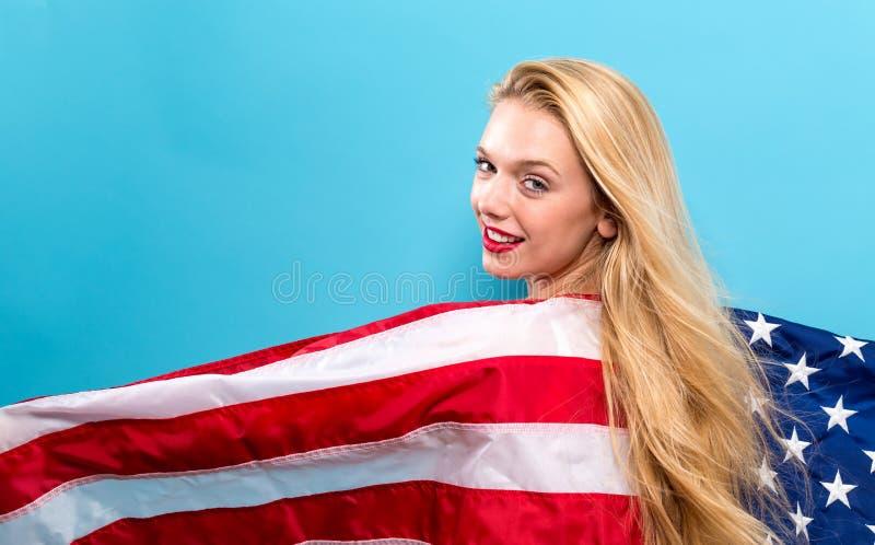 Glückliche junge Frau, die eine amerikanische Flagge anhält stockfotografie