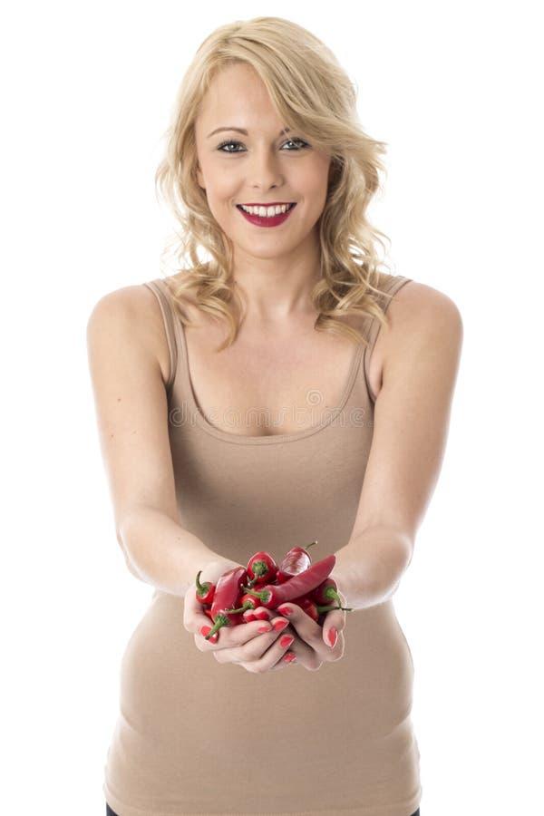 Glückliche junge Frau, die eine Handvoll rote Paprika-Pfeffer hält lizenzfreie stockbilder