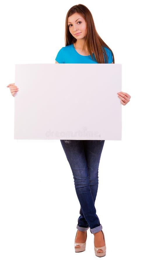 Glückliche junge Frau, die eine leere Anschlagtafel anhält lizenzfreies stockbild