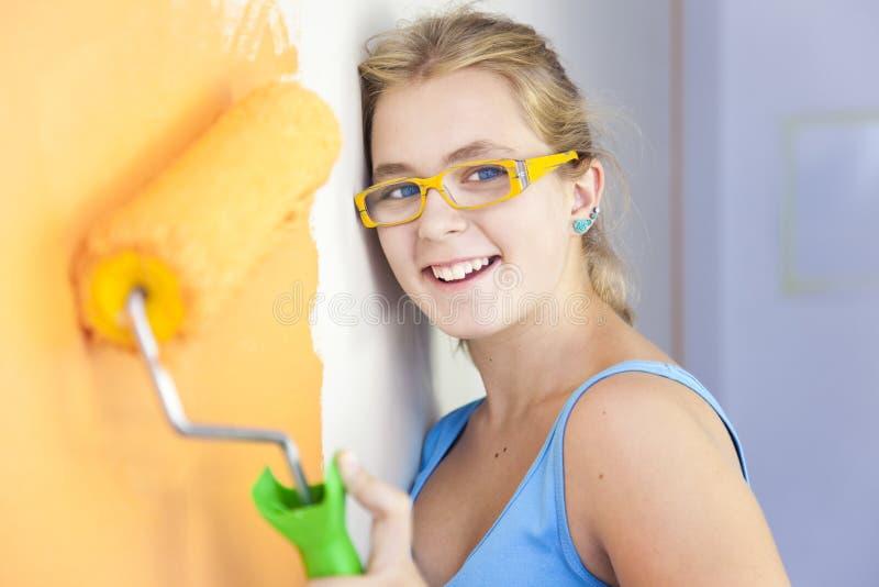 Glückliche junge Frau, die eine Wand malt lizenzfreie stockfotos