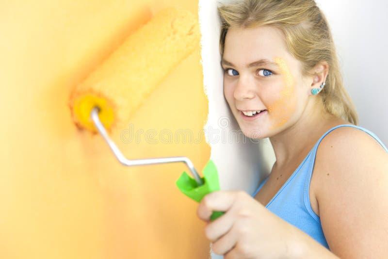 Glückliche junge Frau, die eine Wand malt stockfotografie
