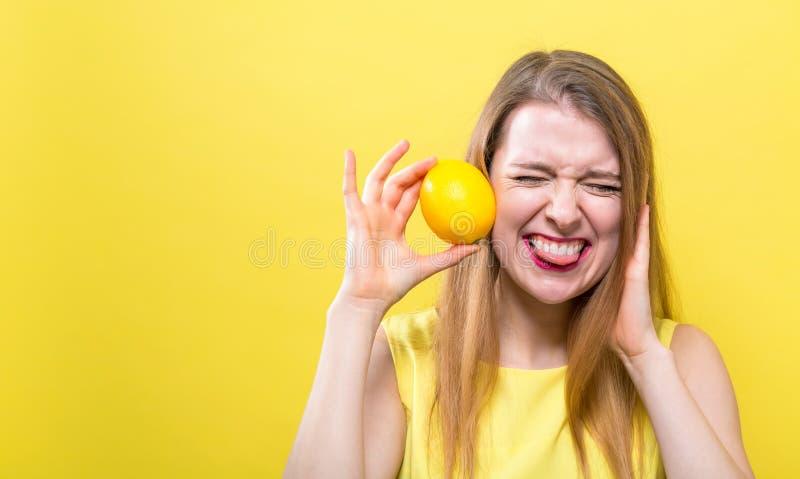 Glückliche junge Frau, die eine Zitrone hält stockbilder