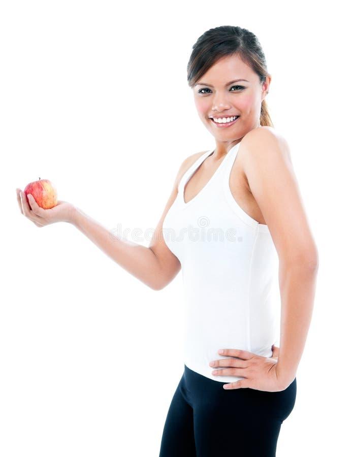 Glückliche junge Frau, die einen Apple darstellt lizenzfreies stockfoto