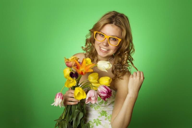 Glückliche junge Frau, die einen Blumenstrauß der Tulpen umarmt stockbilder