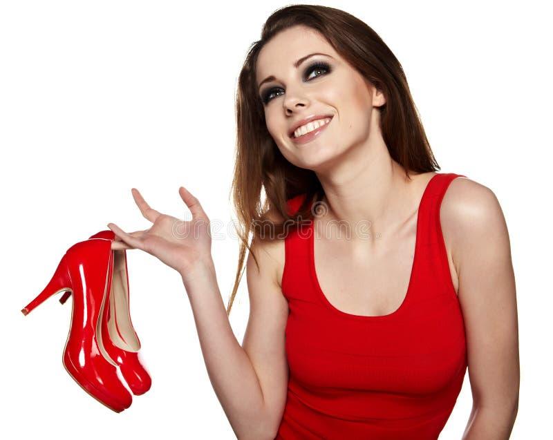 Glückliche junge Frau, die einen roten Schuh anhält lizenzfreie stockfotografie