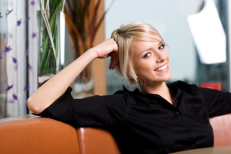 Glückliche junge Frau, die in einer Stange sich entspannt lizenzfreies stockbild