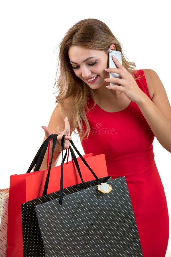 Glückliche junge Frau, die Einkaufstaschen und Handy über weißem Hintergrund hält lizenzfreies stockfoto