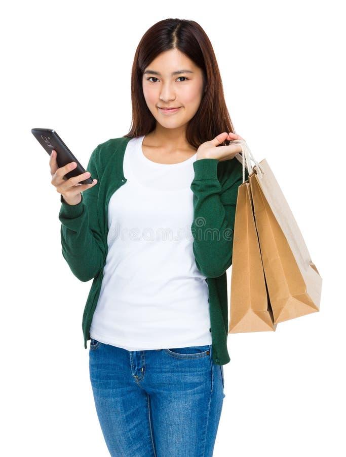 Glückliche junge Frau, die Einkaufstaschen und Handy hält lizenzfreie stockbilder