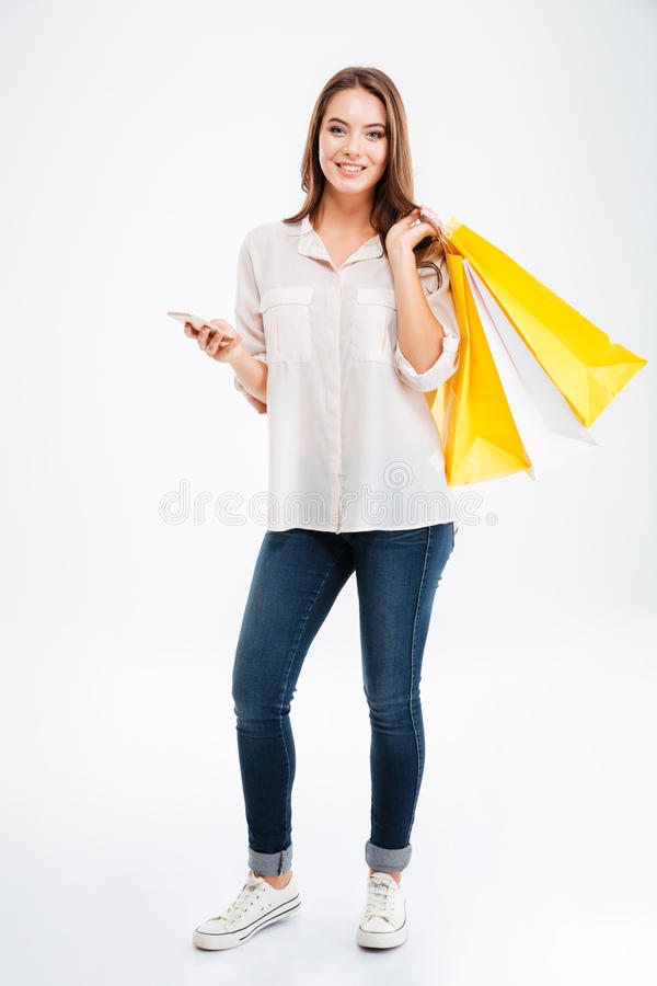 Glückliche junge Frau, die Einkaufstaschen und Handy hält stockbilder