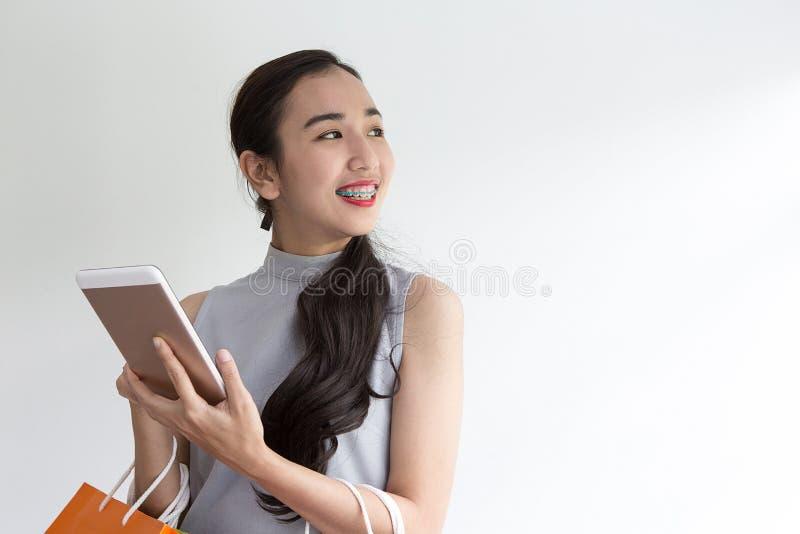 Glückliche junge Frau, die Einkaufstaschen und Handy hält Macht das on-line-Einkaufen auf einer Tablette stockfotos