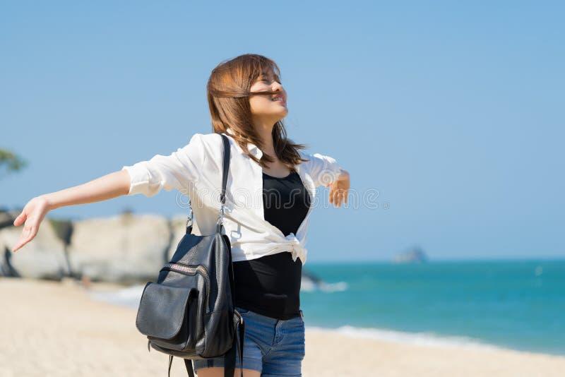 Glückliche junge Frau, die Freiheit mit den offenen Händen auf dem Strand genießt stockfotografie