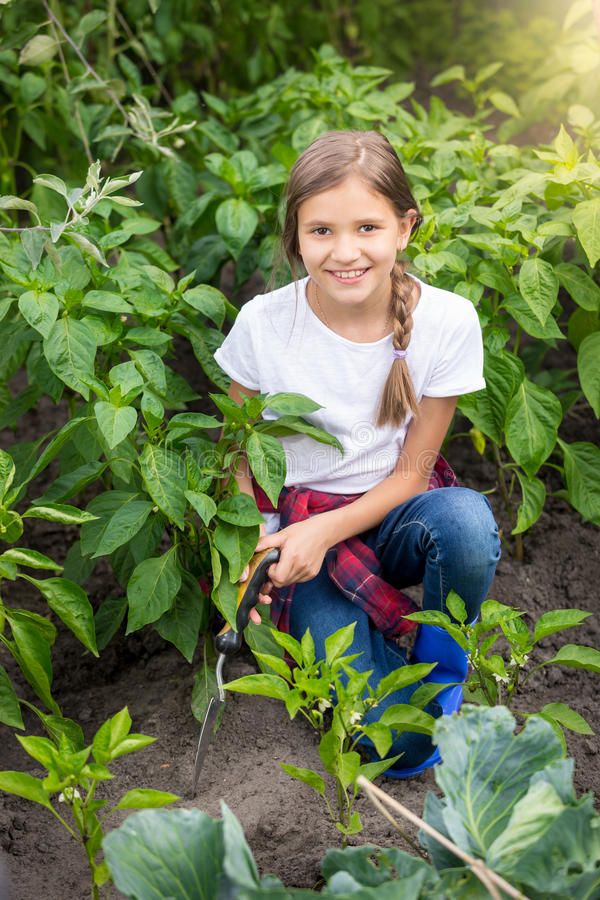 Glückliche junge Frau, die am Garten mit Kelle arbeitet stockbilder