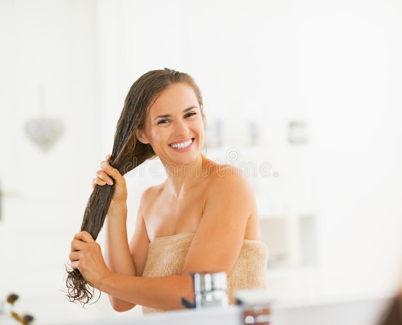 Glückliche junge Frau, die Haarmaske im Badezimmer anwendet lizenzfreies stockfoto