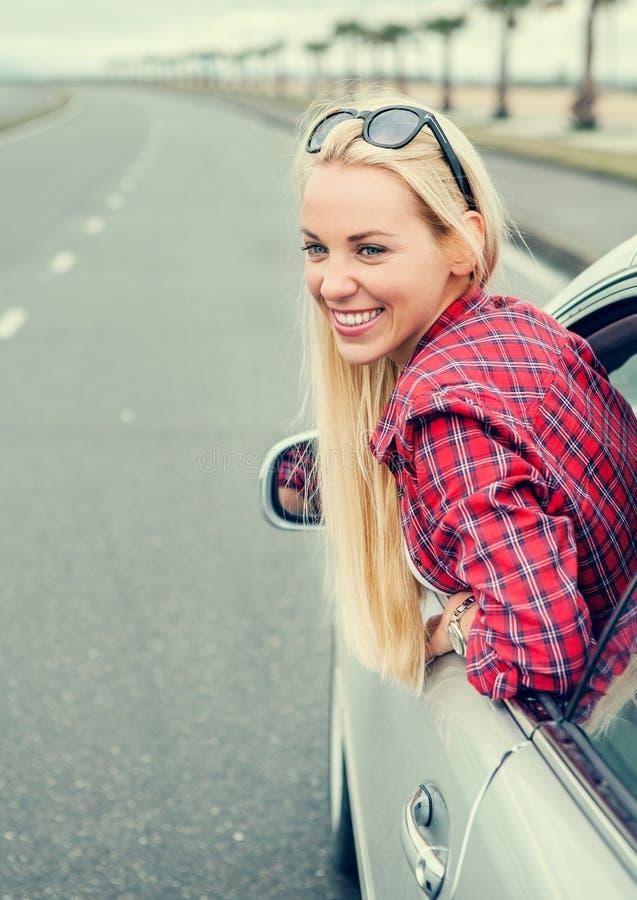 Glückliche junge Frau, die heraus vom Autofenster schaut stockfotos