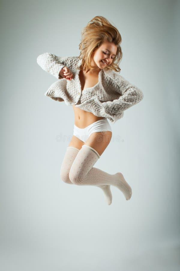 Glückliche junge Frau, die hoch auf grauen Hintergrund springt stockfotos