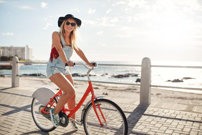 Glückliche junge Frau, die ihr Fahrrad in der Ufergegend reitet lizenzfreie stockfotografie