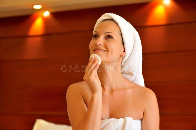 Glückliche junge Frau, die ihr Gesicht reinigt lizenzfreie stockfotografie