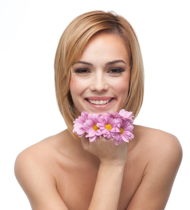 Glückliche junge Frau, die ihr Kinn auf Blumen stillsteht lizenzfreies stockfoto