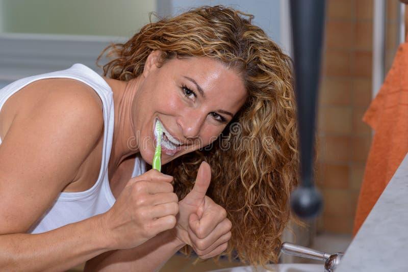 Glückliche junge Frau, die ihre Zähne putzt stockfotografie