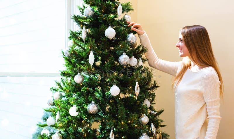 Glückliche junge Frau, die ihren Weihnachtsbaum verziert lizenzfreies stockfoto