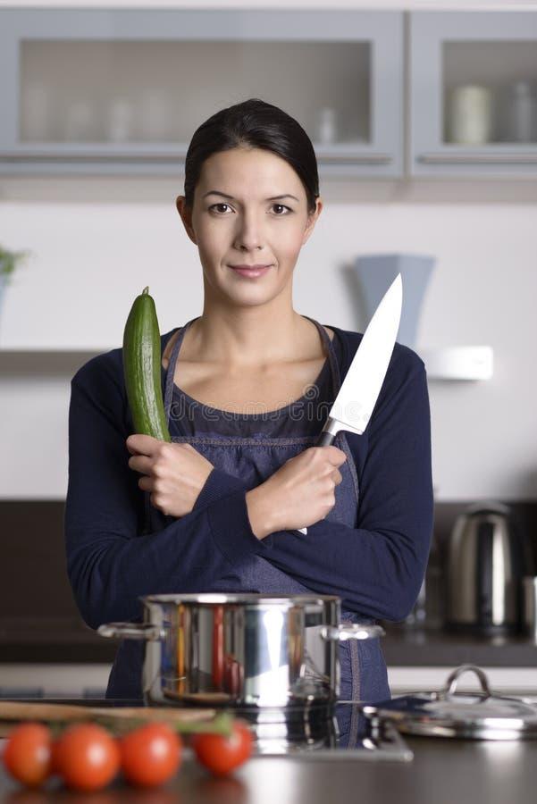 Glückliche junge Frau, die in ihrer Küche aufwirft lizenzfreie stockfotografie
