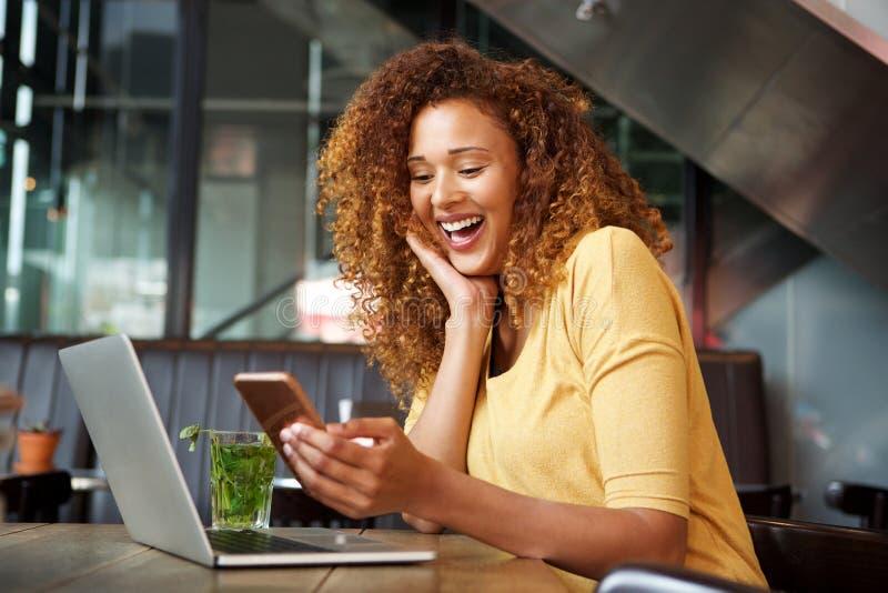 Glückliche junge Frau, die im Café mit Laptop und Handy sitzt stockbild
