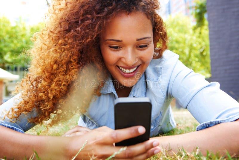 Glückliche junge Frau, die im Gras liegt und Handy betrachtet stockfoto