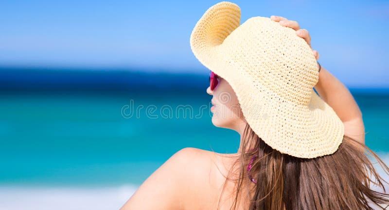 Glückliche junge Frau, die im Strohhut mit geschlossenem lächelt lizenzfreie stockfotografie