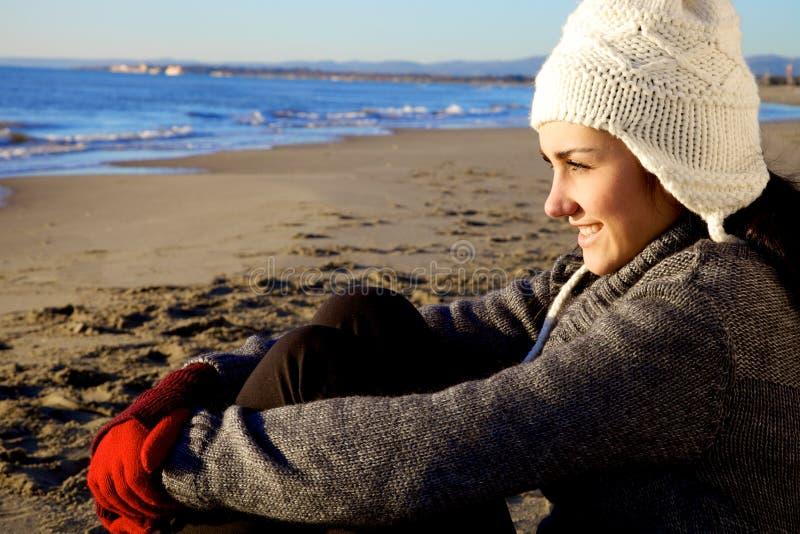 Glückliche junge Frau, die im Winter auf dem Strand sitzt lizenzfreie stockfotografie
