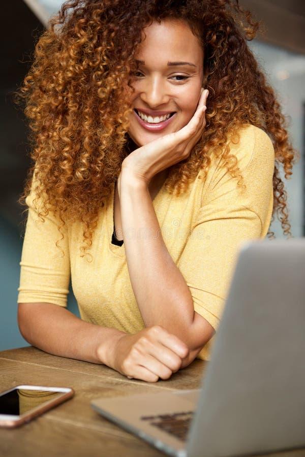 Glückliche junge Frau, die Laptop-Computer betrachtet stockbilder
