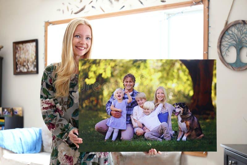 Glückliche junge Frau, die Leinwandkopie des Familien-Porträts hält lizenzfreies stockfoto
