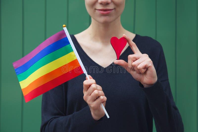 Glückliche junge Frau, die lgbt bunte Regenbogenflagge und rotes hölzernes Herz hält lizenzfreie stockfotos